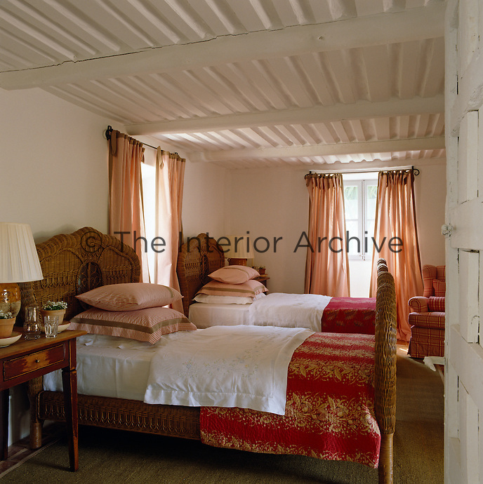 A pair of wicker beds are made up with crisp bed linen and the curtains are a simple red and white striped cotton