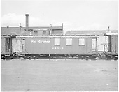 Side view of long caboose #04343 with windows boarded up, flying herald, at Alamosa.<br /> D&amp;RGW  Alamosa, CO  Taken by Payne, Andy M. - 6/3/1969