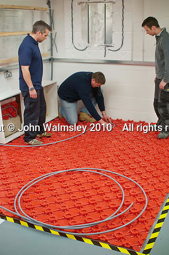Underfloor heating cables being laid in the Renewables section at the Able Skills Training Centre, Dartford, Kent.