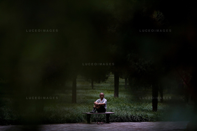 An old man sits quietly in a park in Beijing, China on Wednesday, August 13, 2008.  Kevin German