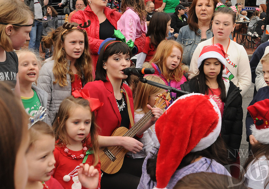 NWA Democrat-Gazette/FLIP PUTTHOFF<br /> Gabby Chronister sings Christmas songs with children Saturday Dec. 12, 2015 before the start of the Bentonville Christmas Parade in downtown Bentonville. Chronister is in the band &quot;Breaking Silence&quot; which played before the parade.