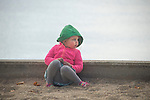 Toddler sitting against retaining wall along beach.