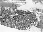 A pilot end fireman's-side view of RGS K-27 #461 crossing Bridge 45-A with a 6 car freight in a snowy scene.<br /> RGS  Ophir, CO  Taken by Richardson, Robert W. - 11/18/1951