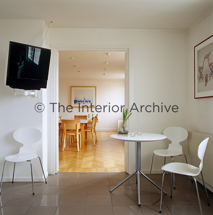 The kitchen has a large television attached to the wall and a tiled floor and opens on to the dining room