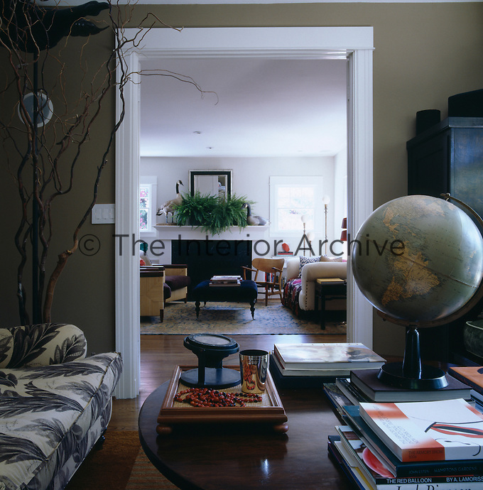 The muted colour scheme of the study contrasts with the white design of the adjacent living room