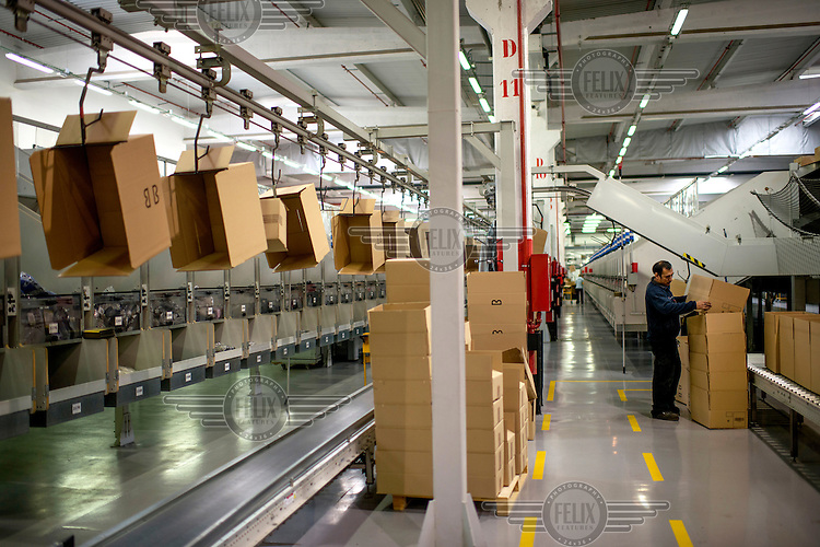 Staff pack boxes at a logistics centre belonging to Mango, the giant Spanish clothing company.