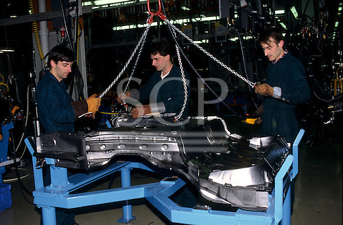Bratislava, Slovakia: Volkswagen factory; three workers positioning a pressed steel floor pan on a jig.