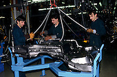 Bratislava, Slovakia: Volkswagen factory; three workers positioning a pressed steel floor pan on a jig.