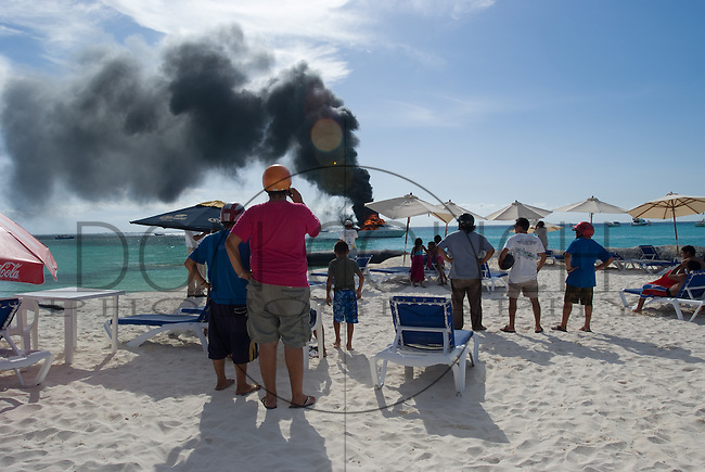 Crowds watch as a boat burns in the waters off Palya Norte, Isla Mujeres, Mexico