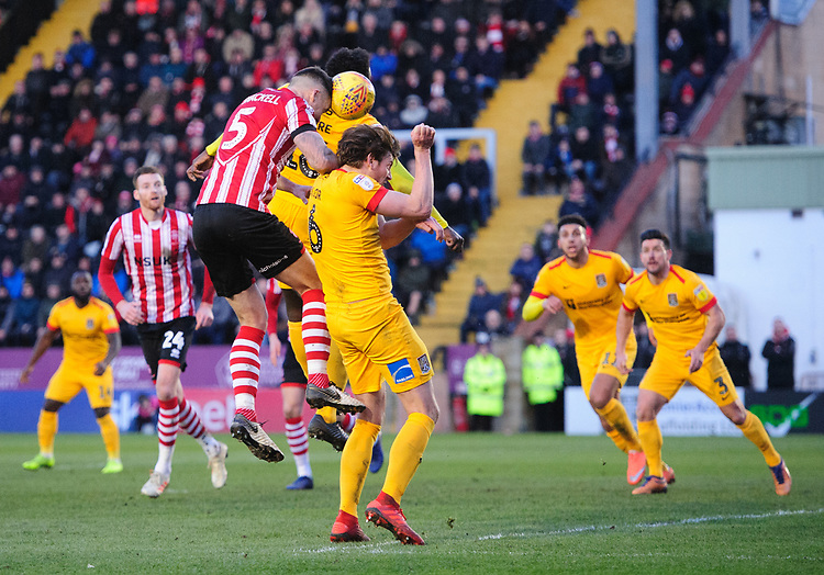 Lincoln City's Jason Shackell vies for possession with Northampton Town's Aaron Pierre, centre, and Northampton Town's Ash Taylor<br /> <br /> Photographer Chris Vaughan/CameraSport<br /> <br /> The EFL Sky Bet League Two - Lincoln City v Northampton Town - Saturday 9th February 2019 - Sincil Bank - Lincoln<br /> <br /> World Copyright © 2019 CameraSport. All rights reserved. 43 Linden Ave. Countesthorpe. Leicester. England. LE8 5PG - Tel: +44 (0) 116 277 4147 - admin@camerasport.com - www.camerasport.com