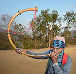 A man plays a curved horn in Majhitar, a village in the Dhading District of Nepal.