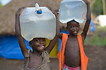 Children carry water in a camp for more than 5,000 displaced people in Riimenze, in South Sudan's Gbudwe State, what was formerly Western Equatoria. Families here were displaced at the beginning of 2017, as fighting between government soldiers and rebels escalated.<br /> <br /> Two Catholic groups, Caritas Austria and Solidarity with South Sudan, have played key roles in assuring that the displaced families here have food, shelter and water.<br /> The camp formed around the Catholic Church in Riimenze as people fled violence in nearby villages for what they perceived as the safety offered by the church.