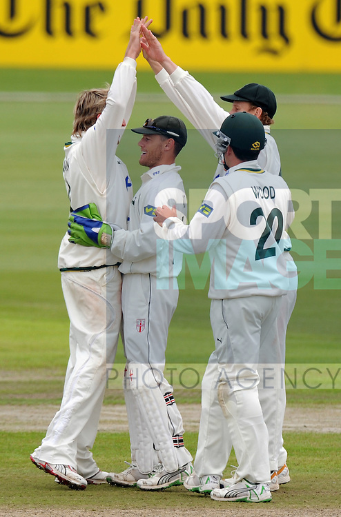 Graeme Swann of Nottinghamshire (L) celebrates taking the wicket of Steven Croft of Lancashire