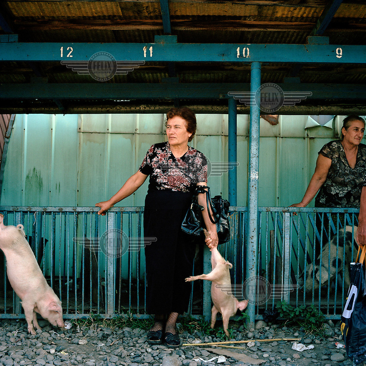 A Mingrelian Georgian woman waits to sell a piglet at Gali market.