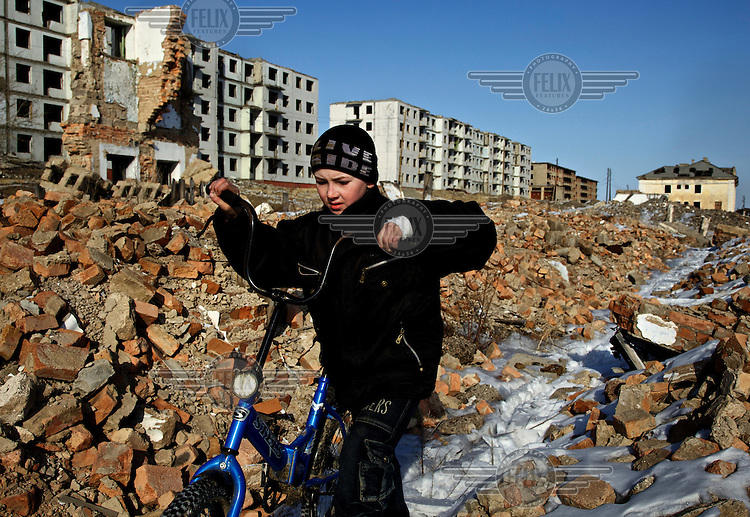 10 year ols Sergei rides his bicycle through the abandoned military garrison town of Mirnaya, 160 km from the Russian border with China. Russia pulled out its army after a border agreement was reached with China in 2004. Subsequently the local economy, which has depended on the military, plunged.