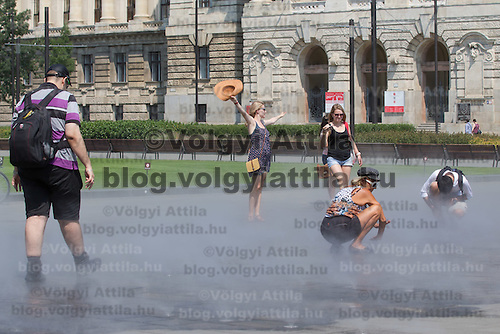 People cool down in the summer heat by the water cloud of the humidifiers in front of the building of the Museum of Ethnography in downtown Budapest, Hungary on July 19, 2015. ATTILA VOLGYI