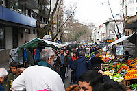 A busy street market with stalls and shoppers on a street in the city. Montevideo, Uruguay, South America