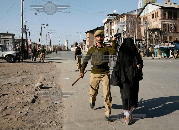 A soldier brings an old woman into safety as paramilitary police and  stone throwing youth clash following Friday prayer at the Jamia Masjid.  Srinagar, Kashmir, India. © Fredrik Naumann/Felix Features
