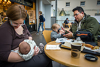 A mother breastfeeds her baby while the dad helps their older son with his drink in a museum cafe.<br /> <br /> London, England, UK<br /> 08/03/2015<br /> <br /> &copy; Paul Carter / wdiip.co.uk