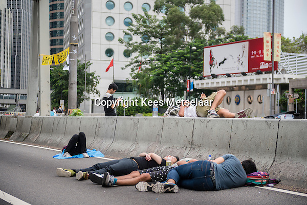 Hong Kong, Government Offices, 2 October 2014<br /> <br /> Students and other supporters of the Occupy Central movement congregating around the government offices area at Tamar. All the roads in the area are blocked from traffic and public transport.<br /> Sleeping on the street in front of the luxury Mandarin Oriental Hotel.<br /> <br /> Photo Kees Metselaar