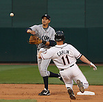 Aces Luke Carlin attempts to break up the double play as the Rainiers second baseman Alex Cintron throws to first.  Tom Smedes photo.