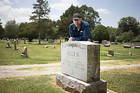 Brian Culpepper, a crime scene technician at the Rogers Police Department, poses for a portrait, Friday, July 17, 2020 at the gravesite of Ed Allen at a cemetery in Rogers. Allen was a constable in Rogers in 1924. He was killed when his car was hit by a runaway horse and buggy. Culpepper is trying to get Allen's name on the law enforcement officer's memorial wall in Washington D.C. but he needs to find a family member. Check out nwaonline.com/200718Daily/ for today's photo gallery. <br /> (NWA Democrat-Gazette/Charlie Kaijo)
