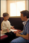 young boy explaining symptoms to doctor