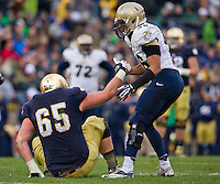 Offensive guard Conor Hanratty (65) is helped up by Navy linebacker Chris Johnson (46).