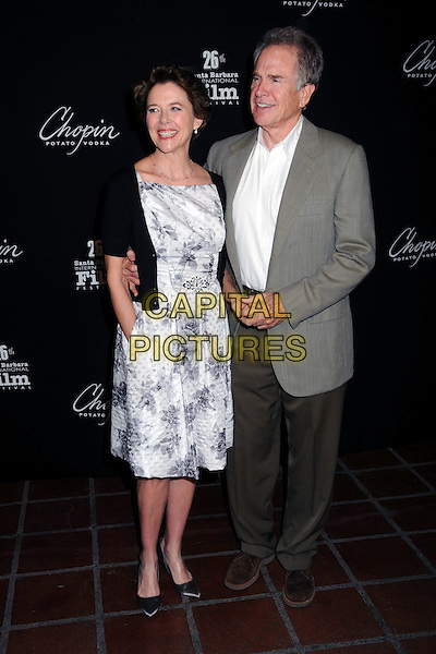 ANNETTE BENING & WARREN BEATTY .2011 Santa Barbara Film Festival - Chopin American Riviera Award Presented to Annette Bening held at the Arlington Theatre, Santa Barbara, California, USA, 28th January 2011..full length white print dress black cardigan floral grey gray holding hands married couple husband wife suit jacket brown trousers .CAP/ADM/BP.©Byron Purvis/AdMedia/Capital Pictures.