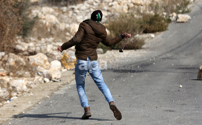A Palestinian protester hurls a stone towards Israeli security forces during clashes following a weekly demonstration against the expropriation of Palestinian land by Israel in the village of Kfar Qaddum, near the West Bank city of Nablus on December 6, 2019. Photo by Shadi Jarar'ah