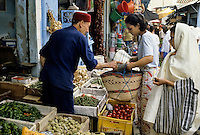 Tunis, Tunisia.  Vegetable Vendor.  Tunisian Women Wearing Modern and Traditional Styles of Dress.