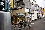 A man cycles past a collection of bars in Shimokitazawa in Setagaya Ward, Tokyo, Japan..Photographer: Robert Gilhooly