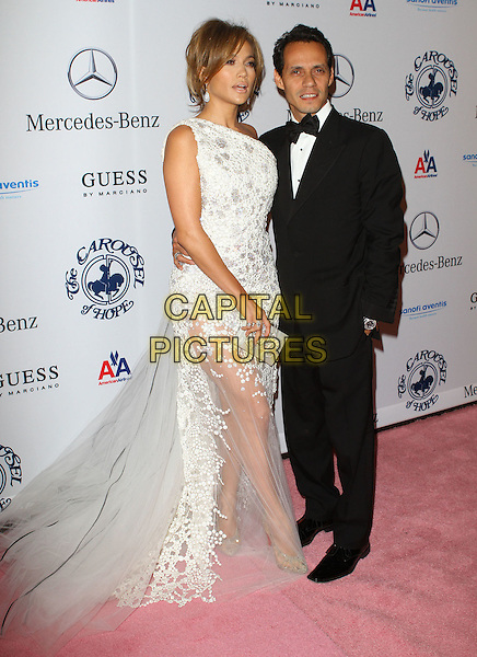 JENNIFER LOPEZ & MARC ANTHONY .at the 32nd Annual Carousel Of Hope Ball held at The Beverly Hilton Hotel, Beverly Hills, CA, USA, .23rd October 2010..full length one shoulder white sheer dress black bow tie tuxdo tux married couple husband wife jlo clutch bag see thru through tulle long maxi train.CAP/ADM/KB.©Kevan Brooks/AdMedia/Capital Pictures.