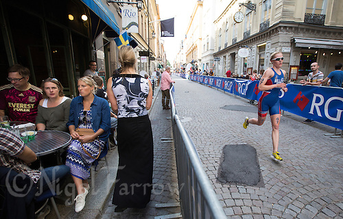 24 AUG 2013 - STOCKHOLM, SWE - Lotte Miller (NOR) of Norway  runs through the streets of Gamla Stan the old part of Stockholm, Sweden during the elite women's ITU 2013 World Triathlon Series round (PHOTO COPYRIGHT © 2013 NIGEL FARROW, ALL RIGHTS RESERVED)