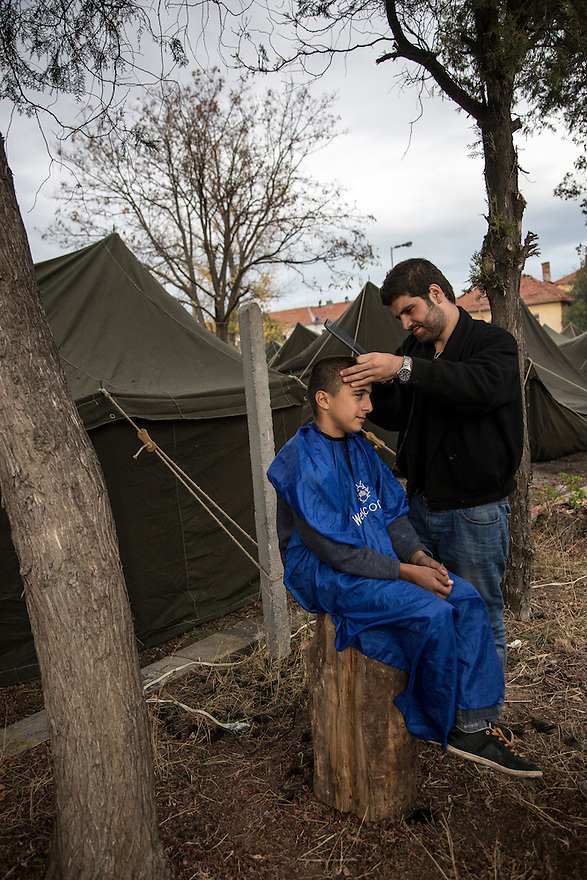 A Syrian barber cuts hair at Harmanli, a former military camp near the Turkish border. Beginning in 2013, officials placed refugees inside military tents with only dirt floors even during the winter months, when it was cold and damp and many people suffered from respiratory infections.