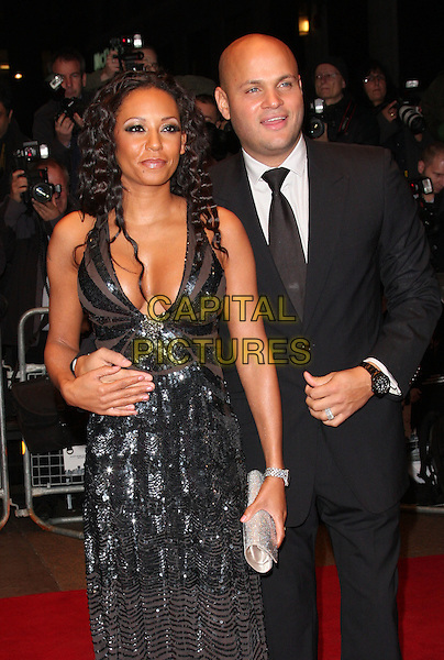 "MEL B (MELANIE BROWN - SCARY SPICE) & STEPHEN BELAFONTE.The World Premiere of ""Dead Man Running"" during the Times BFI 53rd London Film Festival, Odeon West End Cinema, Leicester Square, London, England. .October 22nd 2009.LFF half length married couple husband wife cleavage black suit tie low cut sequined sequins dress silver clutch bag wrist watch arm around waist .CAP/ROS.©Steve Ross/Capital Pictures."