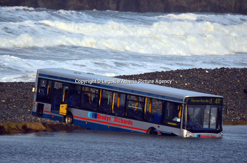 """Pictured: The bus which is partially lodged in a flooded plain by the beach in Newgale, Pembrokeshire, west Wales. Sunday 02 February 2014<br /> Re: Ten people have been rescued after the bus they were on was hit by a wave in Newgale yesterday evening (Saturday).<br /> Cleddau Radio in Pembrokeshire reported: """"Milford Haven Coastguard was contacted just after 7pm this evening with reports that the bus was stuck on the seafront, having been hit by the large wave and was surrounded by water. The wind at the time was gusting over 50mph.<br /> """"Broadhaven and St. Davids Coastguard Rescue Teams, HM Coastguard's Sector Manager for Preseli, along with police, fire and ambulance crews were sent to the scene. The RAF search and rescue helicopter from RMB Chivenor was also asked to assist, but was stood down once the passengers were helped to safety by rescue units on scene. There are no reported injuries."""""""