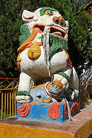 Tibetan national symbol of fearless joy, now forbidden snow lion, with paw on cub, guards the entrance to the Summer Palace of the Dalai Lama, or Norbulingka, founded by 7th Dalai Lama in 1755, Lhasa, Tibet, China.