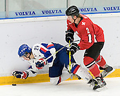 Jakub Rumpel (Medicine Hat Tigers - Slovakia) reaches for the puck as he is knocked down by Marc Welti (HC Thurgau - Switzerland). The Suisse defeated Slovakia 2-1 in a 2007 World Juniors match on January 2, 2007, at FM Mattson Arena in Mora, Sweden.