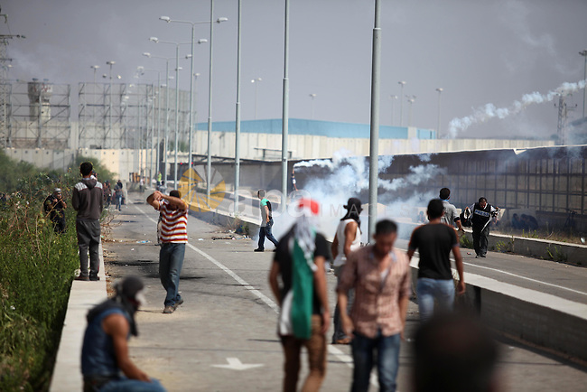 Palestinian protesters clash with Israeli security forces next to the border fence with Israel, at the Erez crossing in the northern Gaza strip, on October 13, 2015. A wave of stabbings that hit Israel, Jerusalem and the West Bank this month along with violent protests in annexed east Jerusalem and the occupied West Bank, has led to warnings that a full-scale Palestinian uprising, or third intifada, could erupt. The unrest has also spread to the Gaza Strip, with clashes along the border in recent days leaving nine Palestinians dead from Israeli fire. Photo by Ashraf Amra