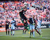Bill Hamid (28) of D.C. United punches the ball away from teammate Casey Townsend (16) and Matt Besler (5) of Sporting Kansas Cityvduring a Major League Soccer match at RFK Stadium in Washington, DC.  D.C. United tied Sporting Kansas City, 1-1.