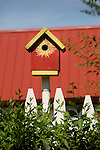 Colorful birdhouse with sunflower pattern.