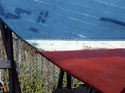 The bow of a wooden boat is being painted in the boat yard.
