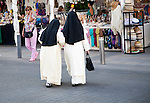 Two Roman catholic nuns linking arms crossing a road in Seville, Spain