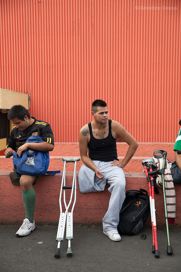 "(L-R) Jorge Morales Gil and Rodrigo Fernandez Loya, both players from Guerreros Aztecas, hang out before the start of training in Mexico City, Mexico on July 31, 2014. Jorge, 17, lost his leg when he was 14 after falling out of a bus. He is a student. Rodrigo, 25, lost his left leg in 2012 when he saved a girl from an onrushing train. Involved in a local 'barrio' gang until his accident, he says that the self-discipline he has developed during his time with Guerreros Aztecas has helped him turn his life around and he is currently studying for his high school diploma. Rodrigo has made the shortlist and is one of the team's biggest hopes to represent Mexico at this December's Amputee Soccer World Cup in Sinaloa. Guerreros Aztecas (""Aztec Warriors"") is Mexico City's first amputee football team. Founded in July 2013 by five volunteers, they now have 23 players, seven of them have made the national team's shortlist to represent Mexico at this year's Amputee Soccer World Cup in Sinaloa this December. The team trains twice a week for weekend games with other teams. No prostheses are used, so field players missing a lower extremity can only play using crutches. Those missing an upper extremity play as goalkeepers. The teams play six per side with unlimited substitutions. Each half lasts 25 minutes. The causes of the amputations range from accidents to medical interventions – none of which have stopped the Guerreros Aztecas from continuing to play. The players' age, backgrounds and professions cover the full sweep of Mexican society, and they are united by the will to keep their heads held high in a country where discrimination against the disabled remains widespread. (Photo by Bénédicte Desrus)"