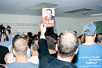 """A man holds up a copy of Ted Cruz's book """"A Time for Truth"""" while Texas senator and Republican presidential candidate Ted Cruz speaks to the media at the kick-off event at his New Hampshire campaign headquarters in Manchester, New Hampshire."""