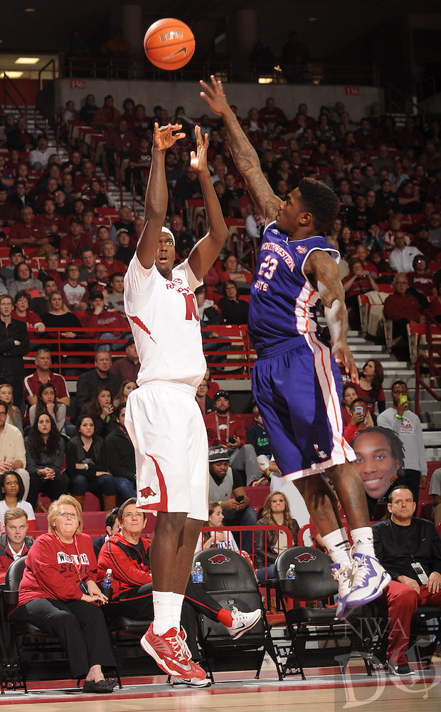 NWA Media/ANDY SHUPE - Arkansas' Bobby Portis, left, takes a shot over Northwestern State's Zeek Woodley (23) during the second half of the Razorbacks' 100-92 win Sunday, Dec. 28, 2014, in Bud Walton Arena in Fayetteville.