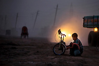 A boy tries to fixed his bicycle, as a car rides past in Dhaka, Bangladesh.