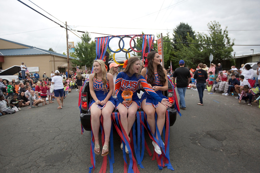 Cheerleaders from the local high school toss candy to waiting kids from the back of a pick-up truck in the Fourth of July Parade in Ridgefield Monday July 4, 2016. (Photo by Natalie Behring/ for the The Columbian)