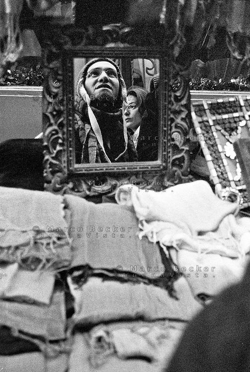 Milano, quartiere Sant'Ambrogio. Fiera degli Oh Bej! Oh Bej!, tradizionale mercatino del periodo natalizio. Riflesso in uno specchio di un uomo che si prova un cappello ad una bancarella --- Milan, Sant'Ambrogio district. Oh Bej! Oh Bej!, traditional Milanese Christmas fair. A man trying a hat in the mirror of a stand